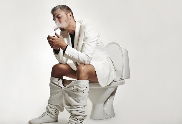 トイレに座っているファッションの若い男の肖像画