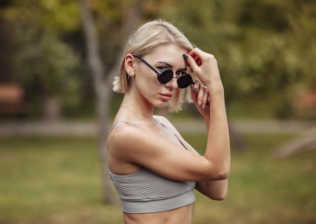 Портрет модной блондинки в стильных солнцезащитных очках в парке