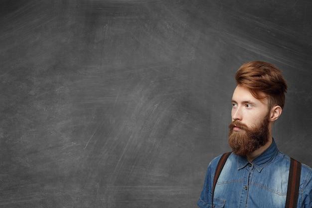 デニムのシャツとサスペンダーを身に着けているファジィなひげとファッショナブルなブルネットの学生の肖像画。彼の顔には真剣で自信のある表情があり、遠くを見つめています。