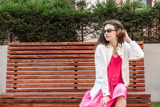 아름 다운 옷 패션에 벤치에 앉아 포즈 유행 갈색 머리 여자 모델의 초상화