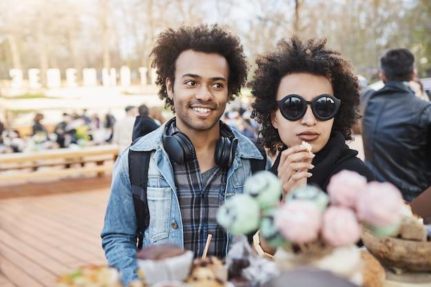 日にファッショナブルなカップルの肖像画。流行の服を着て、キャンディーカウンターの近くに立って、公園でおいしいものを選びます。