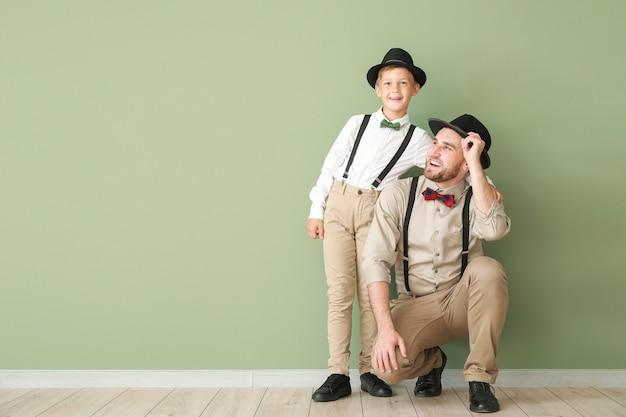 Портрет модного отца и сына возле цветной стены
