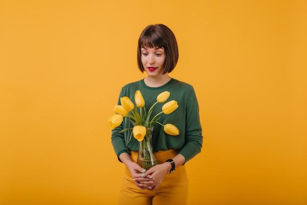 チューリップの花瓶を保持している流行のヘアカットを持つファッショナブルな女性の肖像画。花の花束で隔離の興味のあるブルネットの少女の屋内写真。