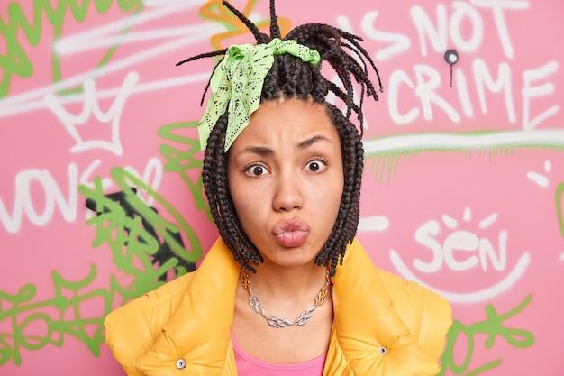 ファッショナブルな10代の少女の肖像画は、カメラの口でしかめっ面をします唇は、カラフルな描かれた落書きの壁に対して都会の場所で若者のサブカルチャーのポーズに属するドレッドヘアをとかしました