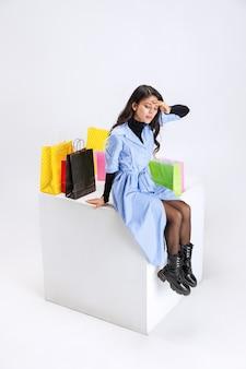 많은 쇼핑 패키지가 흰색 배경에 격리되어 앉아 있는 세련된 여성의 초상화