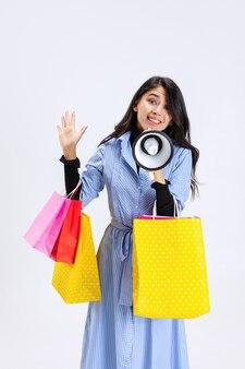 흰색으로 격리된 확성기로 쇼핑백을 들고 있는 세련된 여성의 초상화