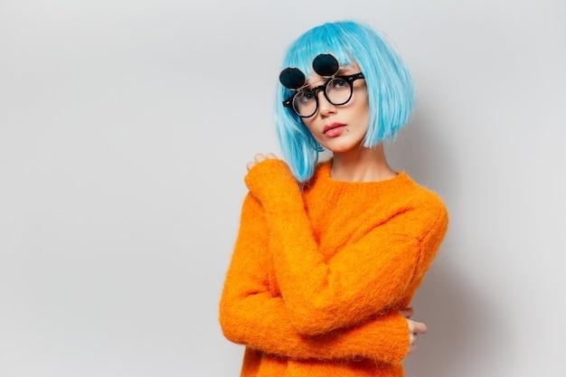 주황색 스웨터와 흰색 배경에 라운드 안경을 착용하는 파란 머리를 가진 유행 젊은 여자의 초상화.