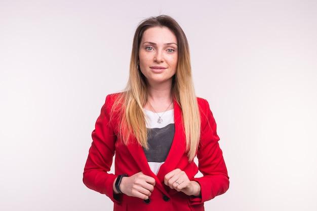 Портрет модной молодой белой женщины, позирующей в красном костюме в студии.
