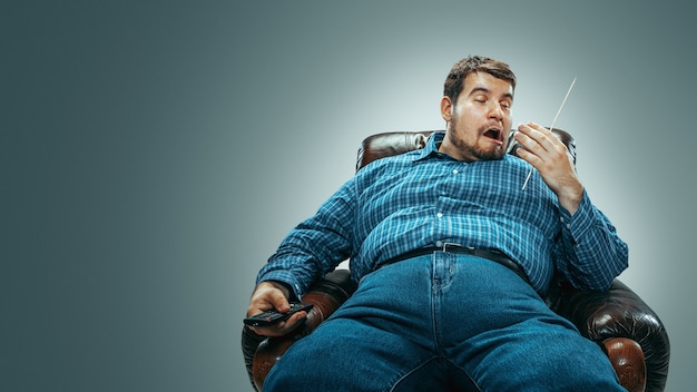 그라디언트 회색 배경에 격리된 갈색 안락의자에 앉아 청바지를 입은 백인 뚱뚱한 남자의 초상화. 감성적인 tv 시청과 채널 변경, 웃음. 과체중, 근심 없는.