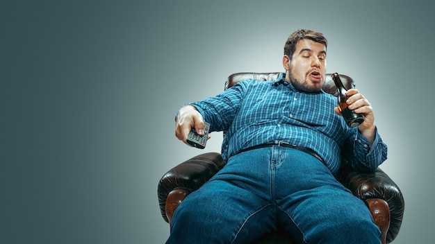 グラデーションの灰色の背景に分離された茶色のアームチェアに座ってジーンズとwhirtを身に着けている太った白人男性の肖像画。テレビを見ながらビールを飲み、チャンネルを変えて笑う。太りすぎ、のんき。