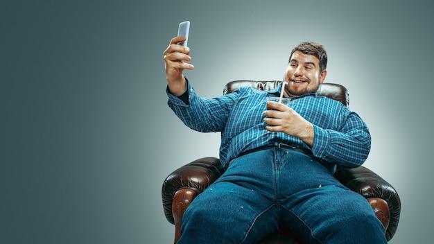 그라디언트 회색 배경에 갈색 안락의자에 앉아 청바지를 입은 백인 뚱뚱한 남자의 초상화. 콜라와 셀카를 찍으며 웃고 있다. 과체중, 근심 없는. 체중 감량의 개념입니다.