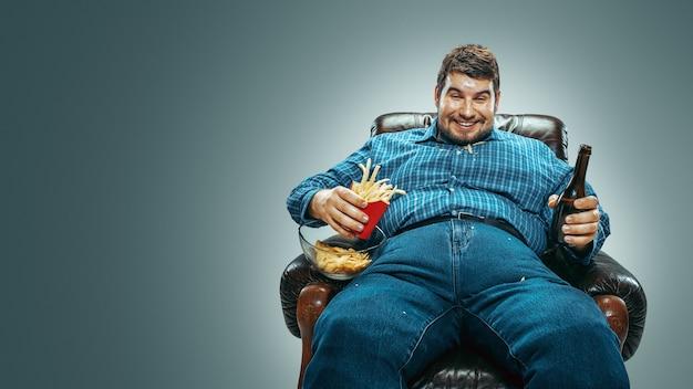 グラデーションの灰色の背景に茶色の肘掛け椅子に座ってジーンズとwhirtを身に着けている太った白人男性の肖像画。テレビを見ながらビールを飲み、チップスを食べ、フライドポテトを食べ、笑う。太りすぎ、のんき。