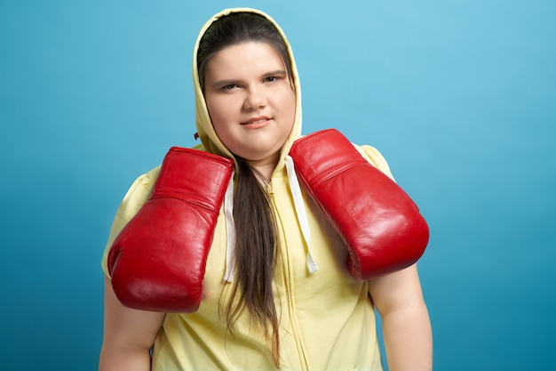 Портрет толстой молодой девушки с каштановыми длинными волосами, покрытыми желтым капюшоном, и в красных боксерских перчатках, свисающих с ее шеи. симпатичная женщина, которая смотрит в камеру, собирается начать тренировку.