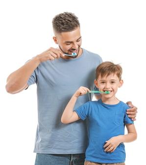 Портрет отца и его маленького сына, чистящего зубы на белом фоне