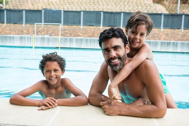 Портрет отца и детей, улыбаясь в бассейне