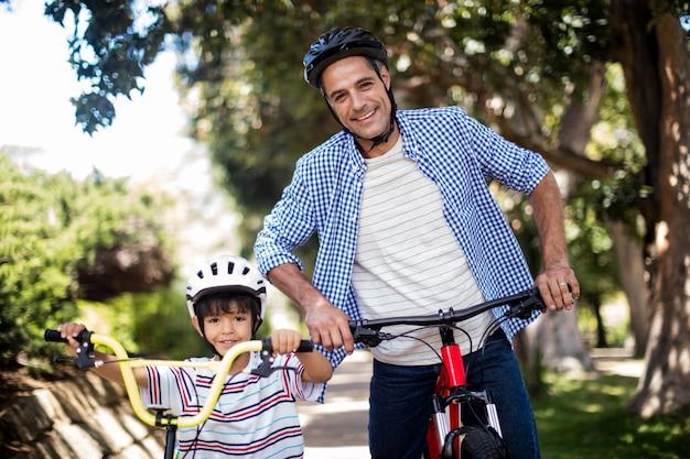 아버지와 아들 공원에서 자전거와 함께 서의 초상화