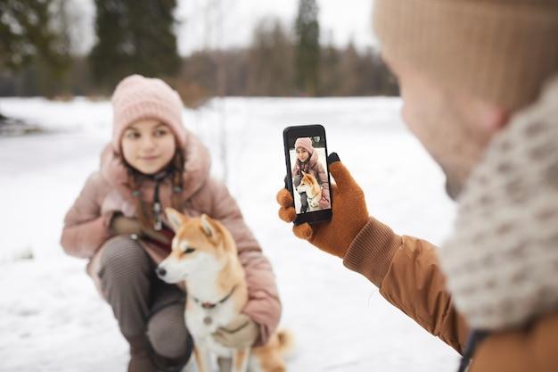 겨울 숲에서 야외 산책을 즐기는 동안 강아지와 함께 귀여운 딸의 사진을 찍는 아버지의 초상화, 스마트폰 화면에 집중, 공간 복사