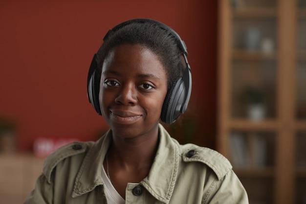 ヘッドフォンを着用し、自宅で作曲しながらカメラを見ているアフリカ系アメリカ人の女性ミュージシャンの肖像画、コピースペース