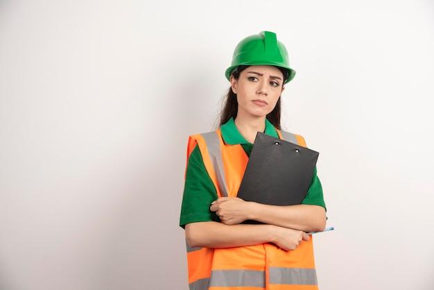 クリップボードを持つ女性建築家のポートレート。高品質の写真