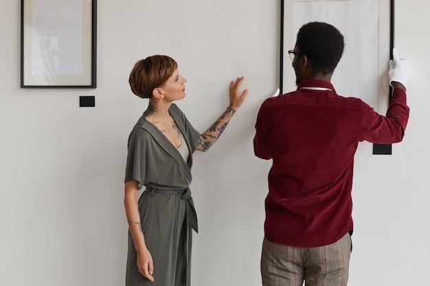Портрет женщины-менеджера художественной галереи, инструктирующей работника вешать рамы для картин на белой стене во время планирования выставки в музее,