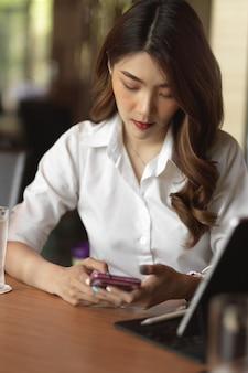Портрет бизнес-леди общается со своими друзьями на смартфоне, проверяя электронную почту на работу