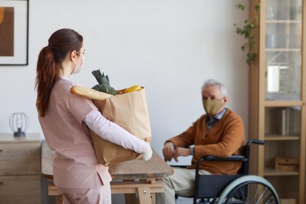 식료품이 든 가방을 들고 휠체어를 탄 노인에게 음식을 배달하는 여성 간병인의 초상화, 공간 복사