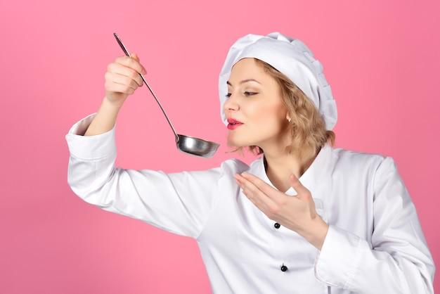 女性シェフの肖像画は、温かい料理とプロの料理のコンセプトフードでスプーンを保持します
