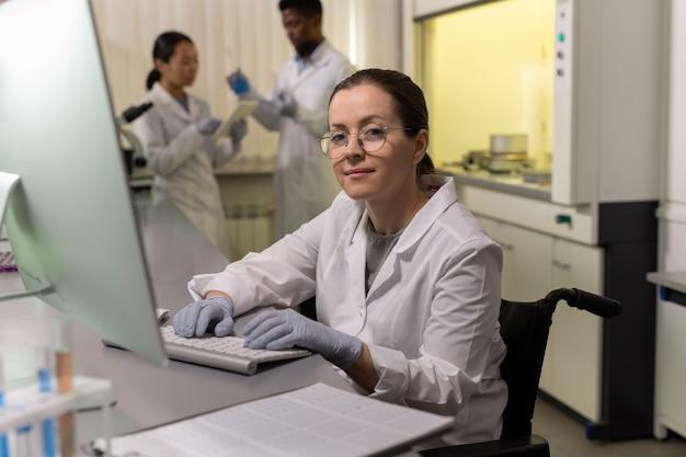テーブルに座って、実験室でコンピューターで作業しながらカメラを見ている眼鏡の女性化学者の肖像画