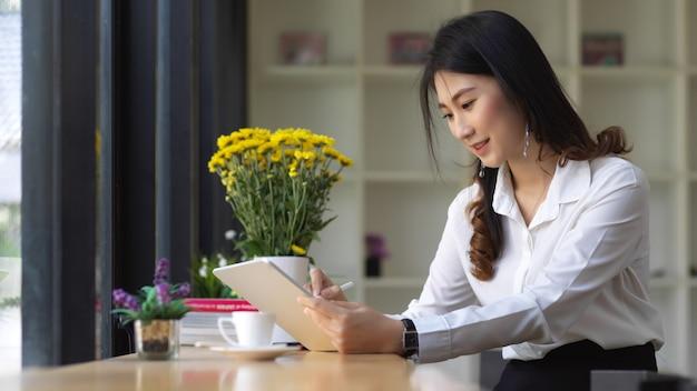 図書館のテーブルの上のタブレットで宿題をしている女子大生の肖像画