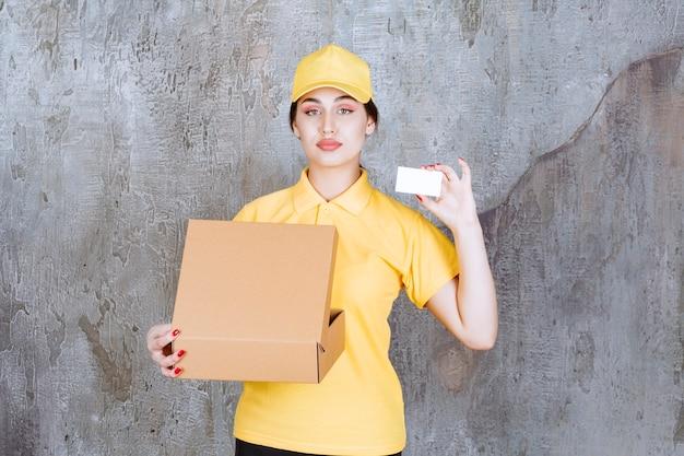 Портрет женского курьера, держащего карточку с картонной коробкой