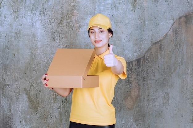 Портрет женщины-курьера, держащего картонную коробку и показывающего большой палец вверх