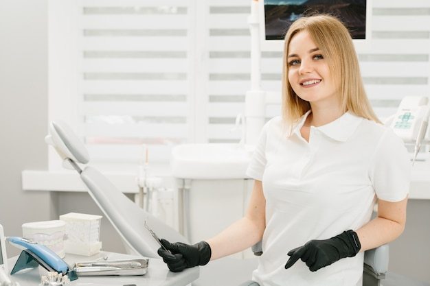 Портрет женский стоматолог. она стоит в своем кабинете и у нее красивая улыбка