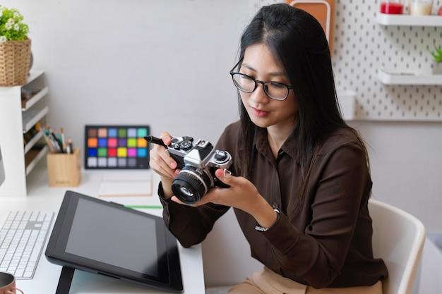 Портрет девушки-дизайнера, работающей с камерой, сидя за офисным столом с дизайнерскими принадлежностями