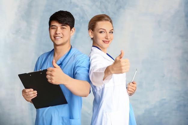 色の背景に親指を示す女性医師と男性の医療助手の肖像画
