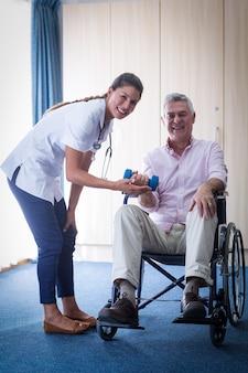 Портрет женского доктора помогая старшему человеку в поднимаясь гантели