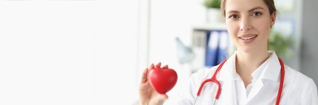 그녀의 손에 작은 마음을 가진 여성 의사 심장 전문의의 초상화