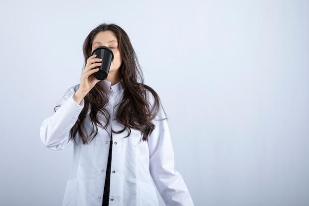Портрет женщины-врача пьет чашку кофе на сером.