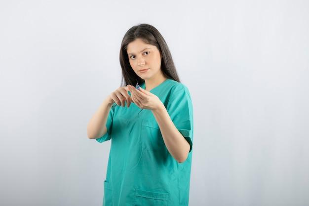 大きな注射器を持っている女性医師の肖像画。 。