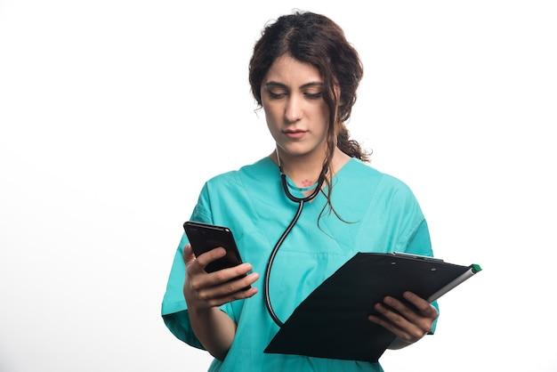 흰색 바탕에 클립 보드와 휴대 전화를 들고 여성 의사의 초상화. 고품질 사진