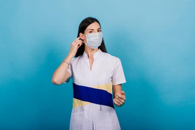 Портрет женщины-врача в медицинской маске, глядя в сторону, изолированную на синем