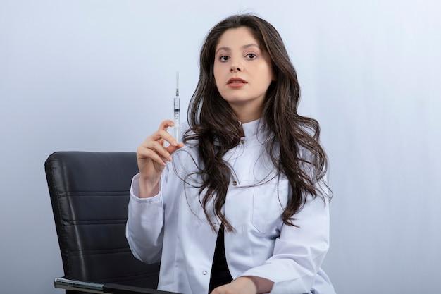 医療マスクと注射器を保持している白いコートの女性医師の肖像画。