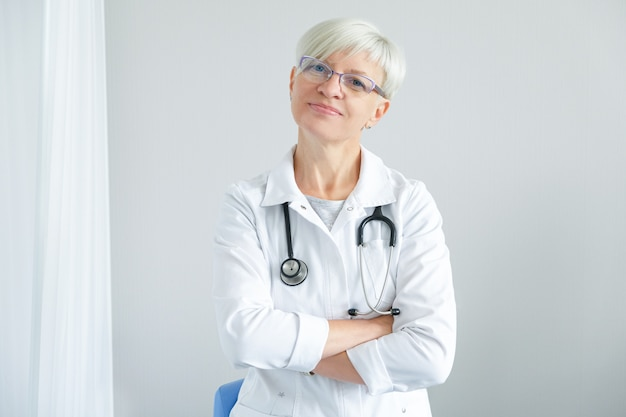 Портрет женского доктора на белой предпосылке.