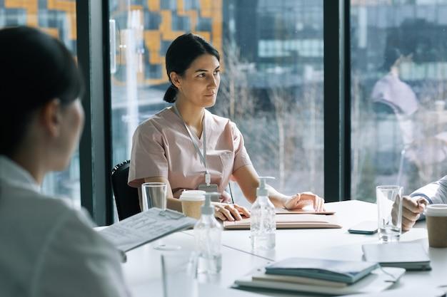 의료 세미나 회의실의 회의 테이블에 앉아 있는 여성 의사의 초상화, 복사 공간