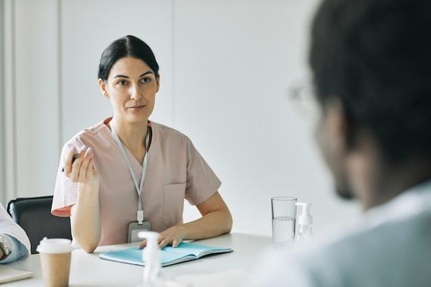 회의실에서 의료 회의 중 동료들과 이야기하는 여성 의사의 초상화, 복사 공간