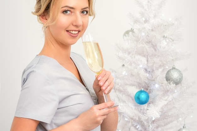 クリスマスツリーの近くに立っているシャンパングラスと女医師の肖像画