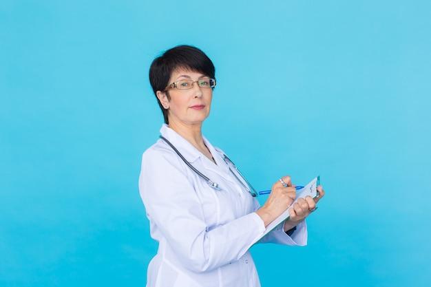 복사 공간이 있는 파란색 배경 위에 클립보드에 쓰는 여성 의사의 초상화