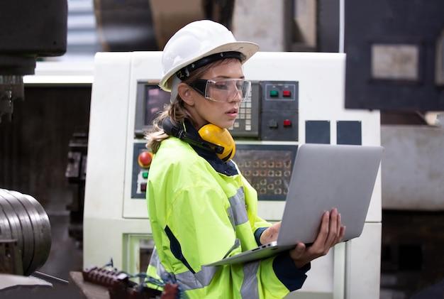 工場でラップトップによる女性エンジニアのオペレーティングマシンの肖像画