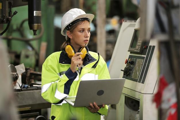 Портрет женщины-инженера, работающего на машине за ноутбуком на заводе