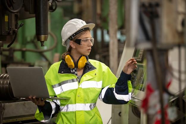 ラップトップコンピューターを使用して工場で機械を操作しながら立っている女性エンジニアの肖像画。