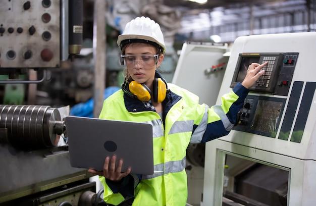 工場の機械環境に対してラップトップで立っている女性エンジニアの肖像画